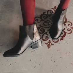 Botinetas-en-punta-de-cuero-negro-graneado-con-elástico-lateral,-taco-medio-foliado-y-recorte-color-oro-en-el-talon